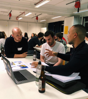 A student shows his portfolio to members of the Studio Nomad team.
