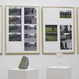 Installation view of photographs on a wall and sculptures on a plinth