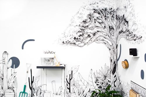 Wall installation showing a tree and garden equipment drawn onto the wall in black marker pen.