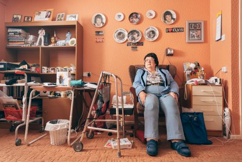 Portrait of an older woman sitting in her armchair surrounded by her belongings.