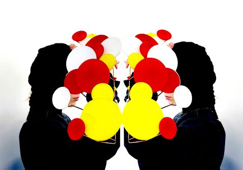Mirror image of person with red, white and yellow objects in front of face