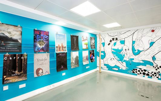A corner section of the degree show, one wall features a range of posters for different animations and the other wall is a large illustrated forest scene.