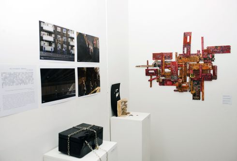 Two plinths holding sculptures while prints and photographs are hung on the walls.