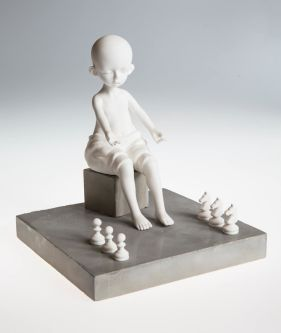 A sculpture of a baby sat in front of six chess pieces