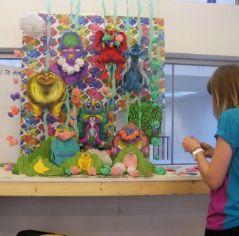 A student works on an elaborate, giant crepe paper illustration of imaginative creatures.