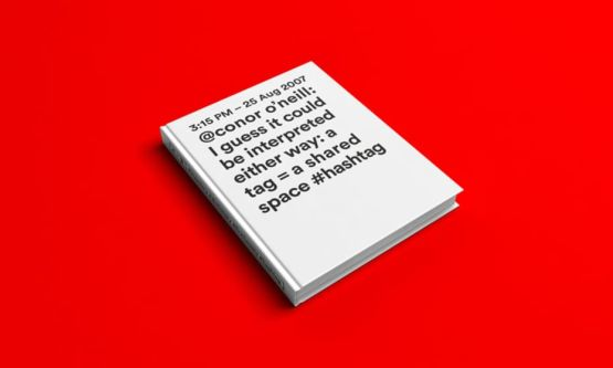 A white book on a red background with a tweet printed on the front in black text