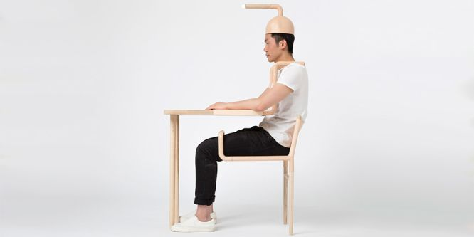 A man sat at a desk is wearing a hat which has a pipe coming out the top of it