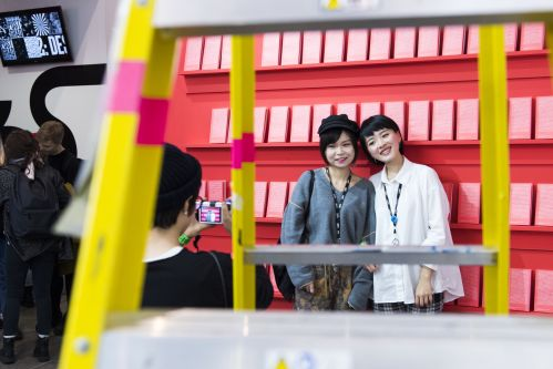 Image of two female students standing in front of book case smiling. The image is taken through a yellow ladder.