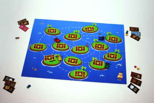 image of board game with treasure map printed on it. The game is on a table with playing cards on each corner