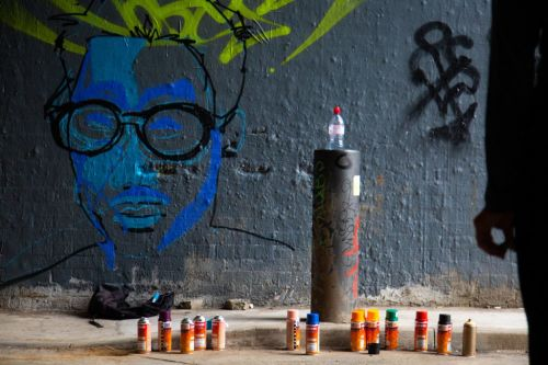 spray paints on the floor in front of a drawn face on wall
