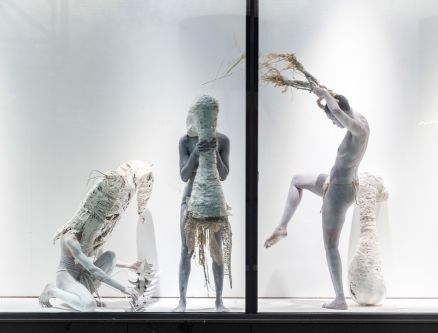 Three figures painted white making shapes in a window