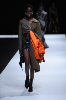 Female model wearing asymmetrical dress in orange, black and dark green tones designed by Yelim Cho