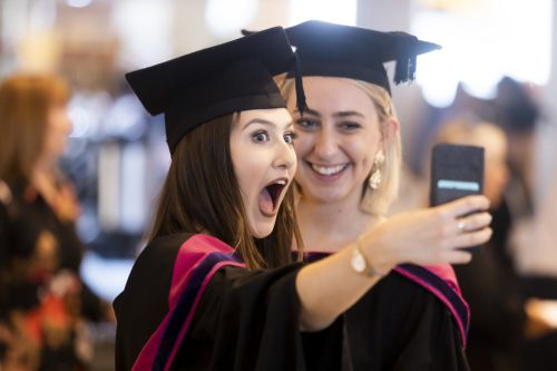 Two female graduates taking a selfie with smart phone.