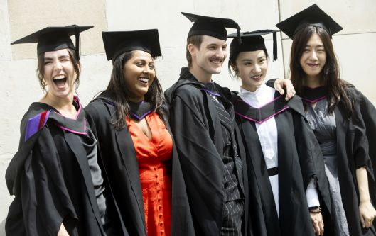 Five mixed graduates posing for a photograph side by side