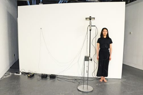 A person stood against a white background hooked up to many wires