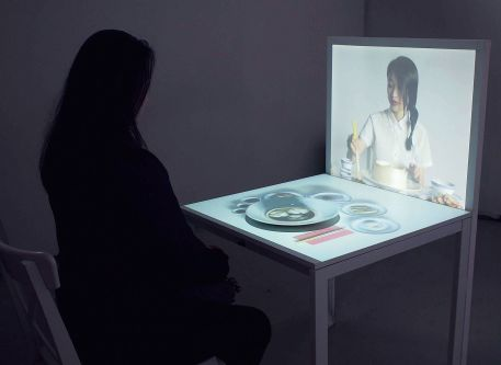 Video projection and meal table. Interactive work by Ann Zeng.