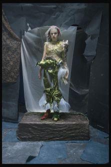 Women wearing green outfit, standing on pedestal