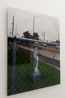 Photograph of a statue on grass behind a wire fence.