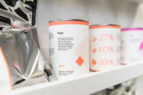 Tins with designed labels in neon pink and orange.