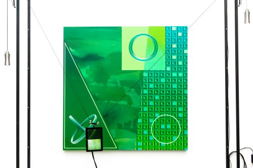 An installation including a green painting with an ipad hanging from wires in front of it.