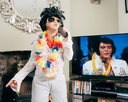 Photograph of a child dressed as Elvis, with a tv showing an image of Elvis behind him.