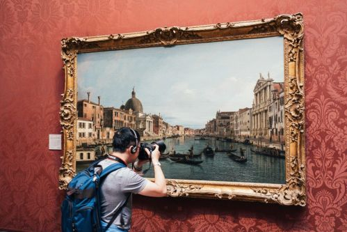 person photographing a painting in a museum