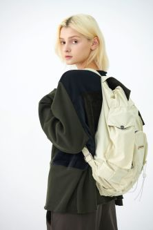Female model in black sweater wearing a cream backpack