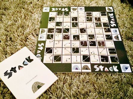 View of a board game. A black and white board divided into smaller squares. On each square is an image of a clock face without numbers. Around the edge are the words 'stack'