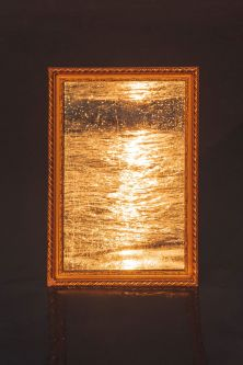 Image depicts a mirror reflecting golden sunlight over water.