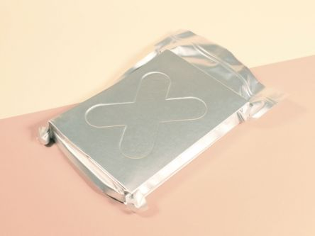 A silver square package with an 'X' embossed on the cover. Background is pale pink and light yellow.