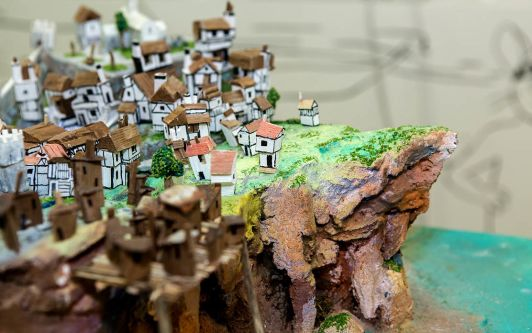 A small town situated near the end of a cliff, the scene is made out of paper.