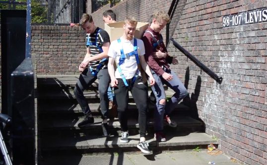 four people walking down stairs with a box attached to their backs