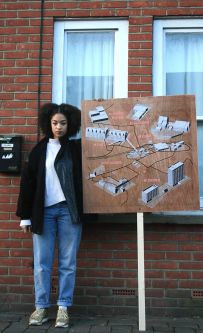A woman stood outside a house holding up a board which has architectural sketches displayed on it