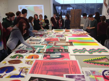 Students gathered around a large table, looking at screen prints.