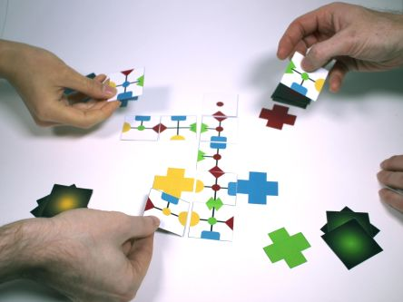 image of three hands playing game holding the pieces in their hands