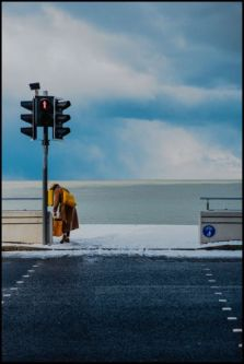 person at traffic lights with blue skies