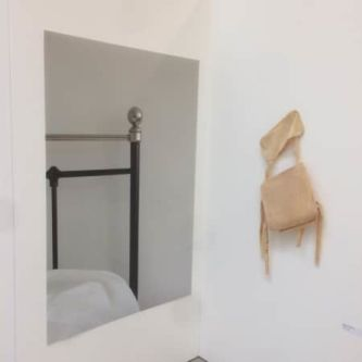 a bedstead in a mirror alongside a chair on a wall