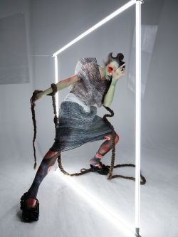 Female model wearing mesh black and white knitted outfit standing under a neon light