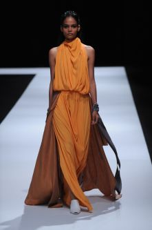 Female model wearing long orange dress designed by Jacqueline Lee