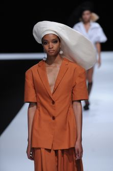 Female model wearing a two piece suit with orange blouse and skirt and big white hat designed by Rachel Simona Cosenza