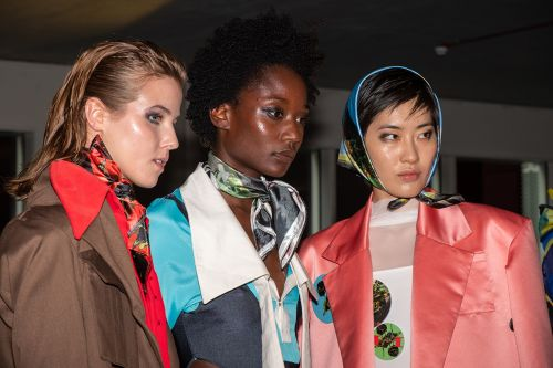 Three female models, on the left model wearing brown coat, in the middle model wearing blue coat with silk scarf, on the end model wearing peach silk coat