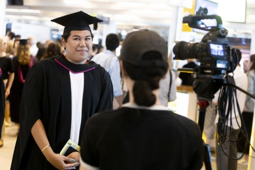 Graduate being recorded and speaking into a camera