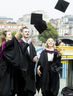 Two female and one male graduates throwing their hats in the air