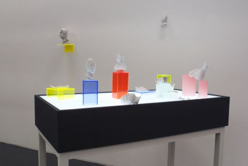 A table of coloured perspex boxes and 3D printed sculptures