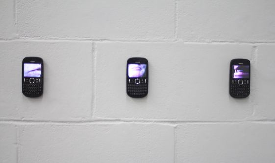 Video series displayed on mobile phones mounted on wall in gallery by Helen Eccles.