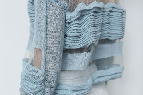 Waist of a model in sheer blue jumper