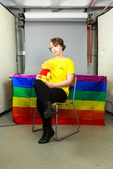 Portrait of student sat in front of a rainbow flag.