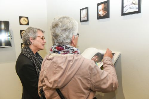 Visitors looks at art work on a gallery wall.