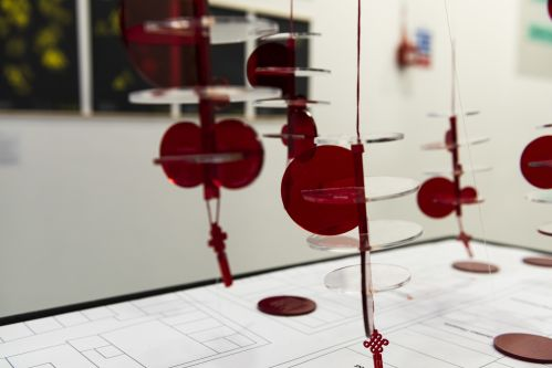 Hanging red perspex circles in an exhibition space.