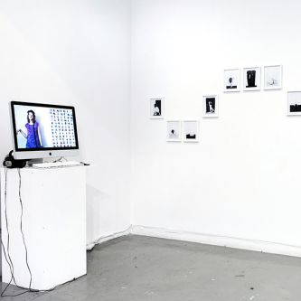 Installation view of artwork on the wall and screen on a plinth